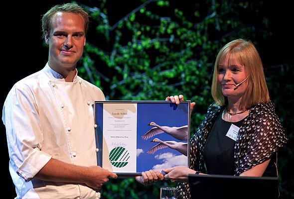 Kjøkkensjef Steffen Chapman, V Bar og Bistro, mottar Svanemerket fra Miljømerkings direktør Alvhild Hedstein (foto fra Miljømerking)